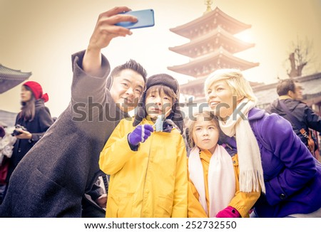 Happy multiethnic family taking a picture in front of Sensoji Temple in Tokyo. - stock photo