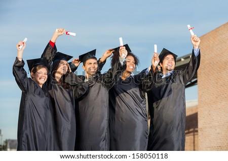 Happy multiethnic students with diplomas standing together on university campus - stock photo