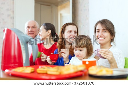 happy multigeneration family communicate over tea with cakes