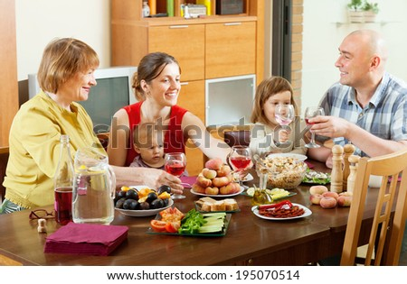 happy multigeneration family posing together over celebratory table at home - stock photo