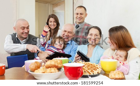 Happy multigeneration family posing together with various electronic communication devices over tea  at home