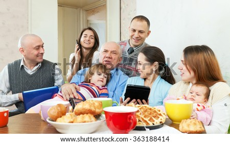 Happy multigeneration family posing together with various electronic communication devices over tea