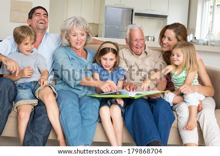Happy multigeneration family reading storybook in living room at home - stock photo
