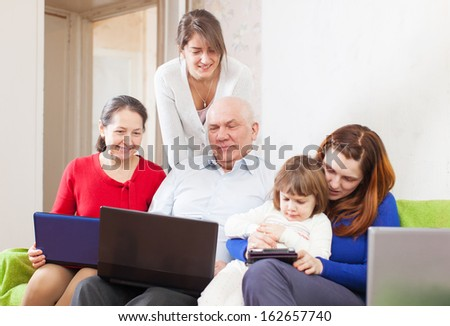 Happy multigeneration family uses few portable computers in home interior   - stock photo