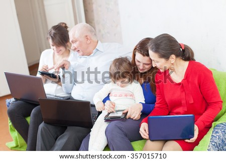 Happy multigeneration family uses few various portable computers in home