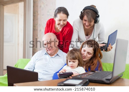 Happy multigeneration family uses  various electronic devices in home interior   - stock photo