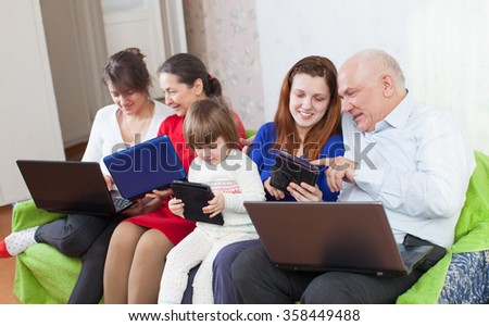 happy multigeneration family using few laptops in home