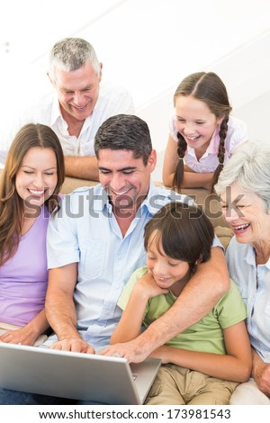 Happy multigeneration family using laptop at home