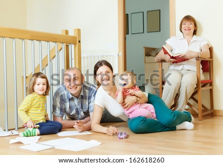 happy multigeneration family with two children enjoying at floor in home together - stock photo