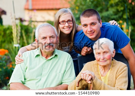 Happy multigenerational family visiting the elder member - the grandmother - in a nursing home.
