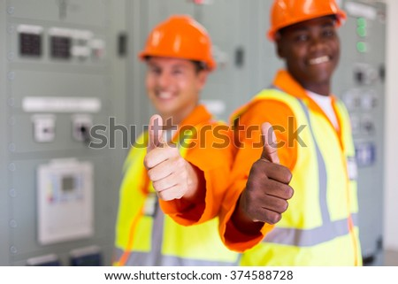 happy multiracial electrical co-workers thumbs up - stock photo