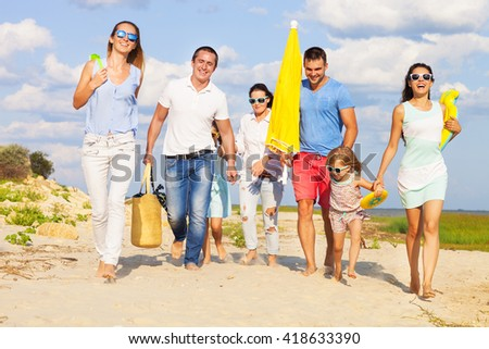 Happy multiracial group of friends with children walking at the beach