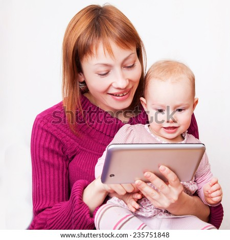 Happy Mum and baby girl looking at tablet - stock photo