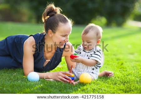 Happy mum and her child playing in park together. Outdoor portrait of happy family - stock photo