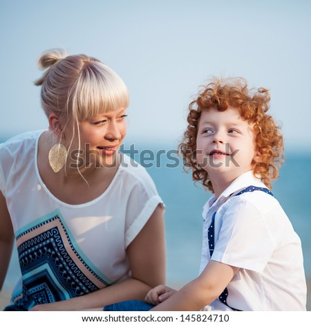 happy mum and her red head son having fun together outside - stock photo