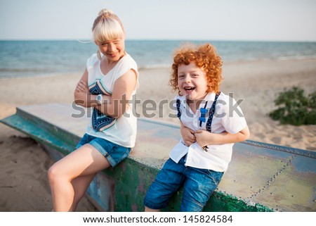 happy mum and her red head son having fun together outside on the beach, sitting on old boat - stock photo
