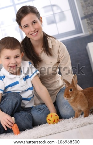 Happy mum and little son playing with domestic rabbit at home, carrot and ball. - stock photo