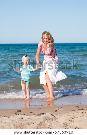 Happy mum and the son on a beach - stock photo