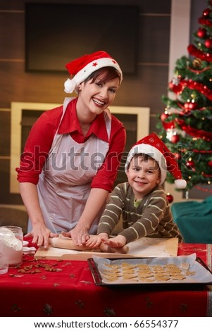 Happy mum baking with son for christmas, looking at camera, smiling.? - stock photo