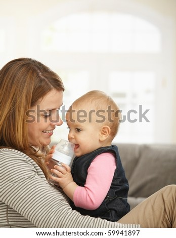 Happy mum holding baby girl in arms smiling.? - stock photo