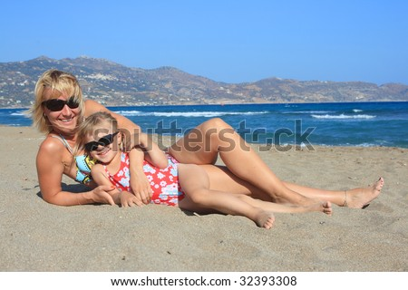 Happy mum with a daughter on a beach