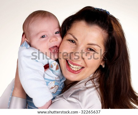 Happy mum with the laughing child on hands - stock photo