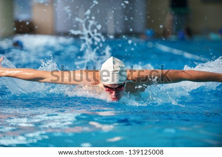 Happy muscular swimmer wearing glasses and cap at swimming pool and represent health and fit concept - stock photo