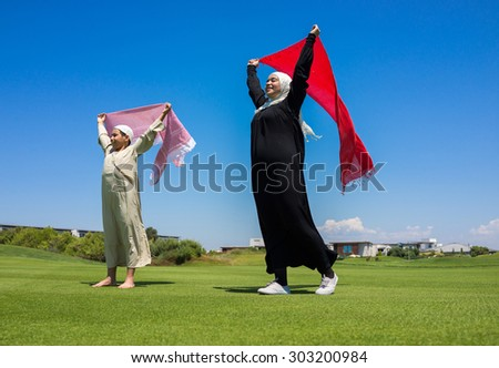 Happy Muslim family on meadow with scarf - stock photo