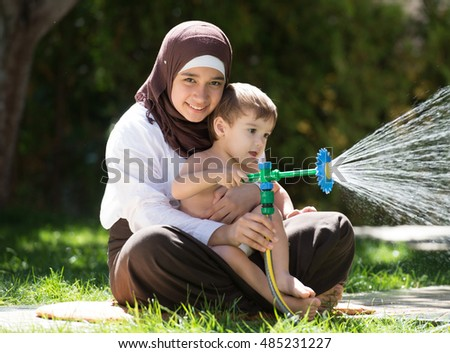 Happy Muslim female with a baby on summer meadow splashing water having fun and happy time