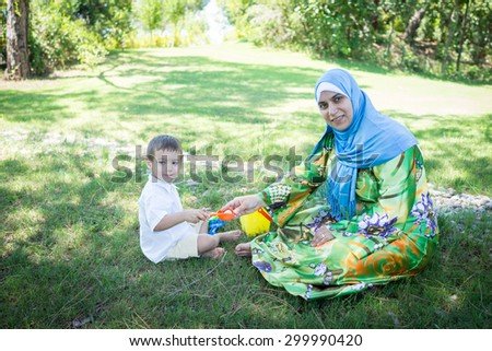 Happy Muslim mom with little son - stock photo