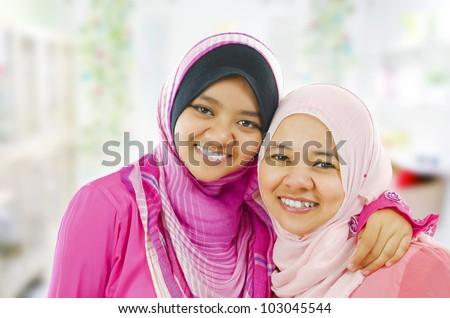 Happy Muslim women standing inside house - stock photo