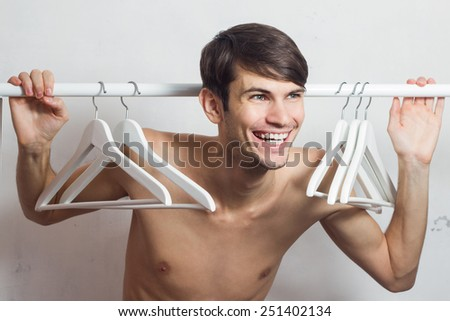 Happy naked handsome young man stands near the empty hangers.
