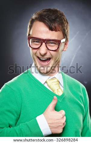 Happy nerd wearing eyeglasses showing thumbs up sign. Smiling young man showing ok gesture. - stock photo