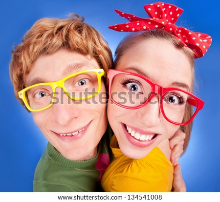 Happy nerdy couple embracing - stock photo