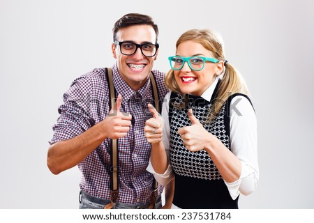 Happy nerdy couple showing thumbs up,Successful nerds - stock photo