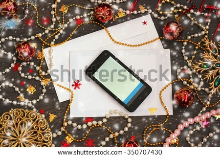Happy New Year and Merry Christmas ! New Year's background: envelopes, mobile phone, a beads and confetti on a wooden flooring, the top view. - stock photo