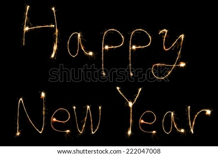happy new year ! burning sparkler stick and writing sparkling text on black background - stock photo