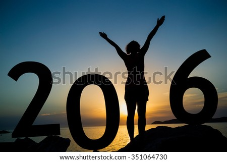 Happy new 2016 year card. A girl standing on a beach, watching the sunset, standing as a part of 2016 sign - stock photo
