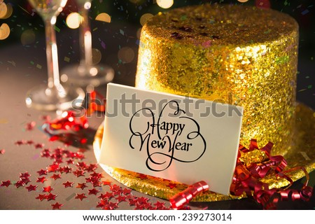 Happy new year card on table set for party with gold hat and champagne - stock photo