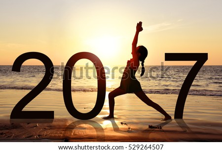 Happy new year card 2017. Silhouette of A girl doing Yoga warrior I pose on tropical beach with sunset sky background. Preteen practicing yoga on the beach, standing as a part of the Number 2017 sign.
