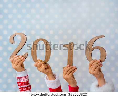 Happy New Year. Children hands holding wooden numbers 2016 against blue polka dot background. Winter holidays concept - stock photo