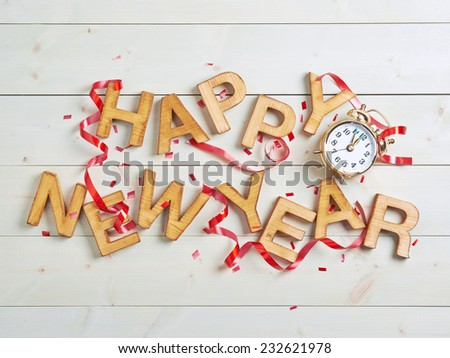Happy New Year composition of the wooden letters surrounded with the multiple decorations over the white colored wooden boards surface - stock photo