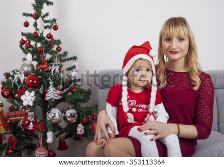 Happy New Year concept. Merry girl in red dress and hat of Santa Claus with Christmas tree.