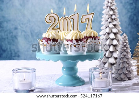Happy New Year 2017 cupcakes on a modern stylish, festive, blue gold and white Winter theme table setting, with copy space.