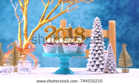 Happy New Year 2018 cupcakes on a modern stylish, festive, blue gold and white Winter theme table setting.