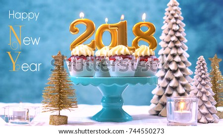 Happy New Year 2018 cupcakes on a modern stylish, festive, blue gold and white Winter theme table setting, close up with Happy New Year text.