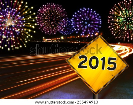 Happy New Year 2015 fireworks and city cars highway lights with yellow road sign. Greeting card design background. - stock photo