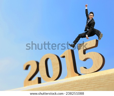 Happy new year for 2015 - success business man jump in the air cheering and celebrating on wood number - stock photo