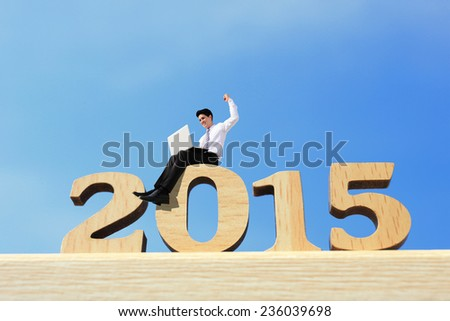 Happy new year for 2015 - success business man with laptop computer and sitting on wood number - stock photo
