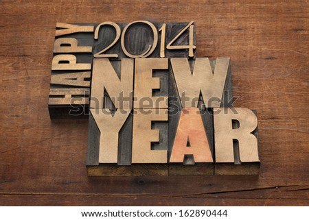 Happy New Year 2014 greetings - text in vintage letterpress wood type blocks on a grunge wooden background - stock photo